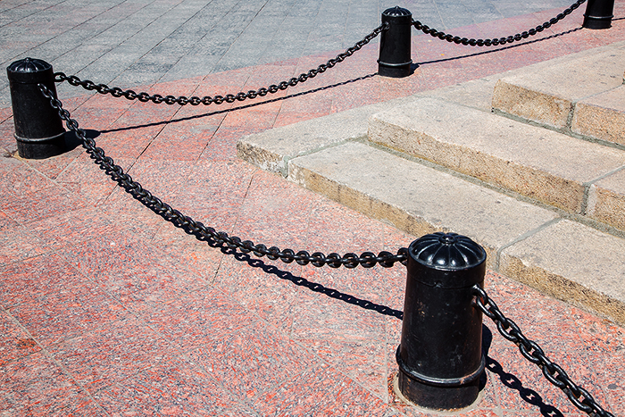Cast-iron Black bollards with chains against the background of paving slabs